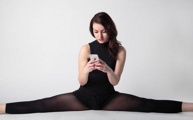 Frau imSpagat mit Handy